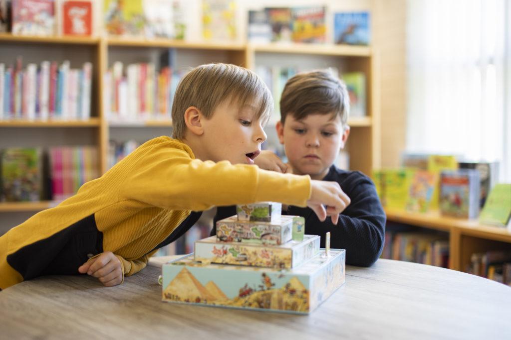Lapset pelaavat lautapeliä kirjastossa
