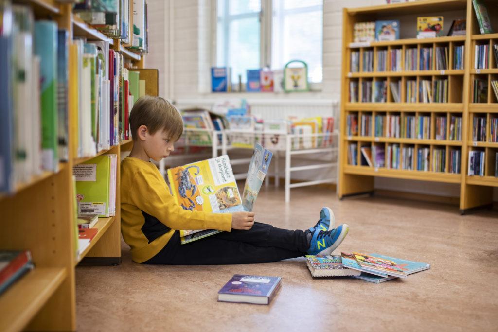 Lapsi lukee kirjoja kirjaston lastenosastolla