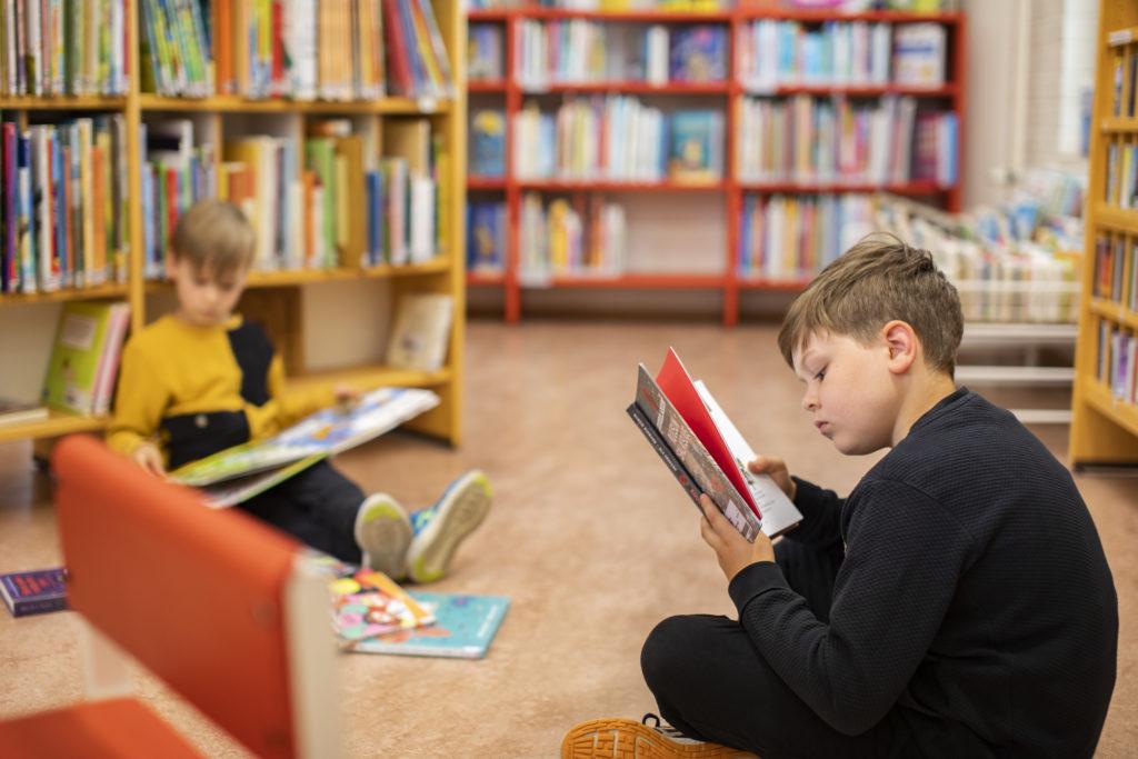 Kaksi poikaa lukemassa kirjoja lastenosaston lattialla istuen