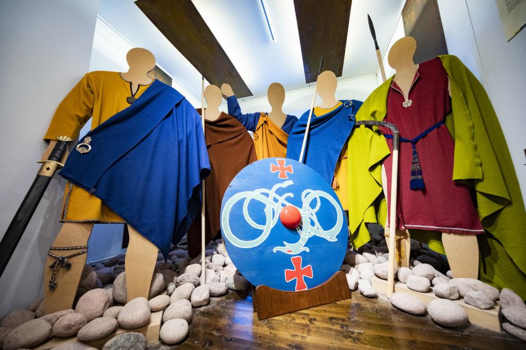 Miesten puvukopiot ja kilven ennallistus. Kilven painoa voi kokeilla näyttelyssä.