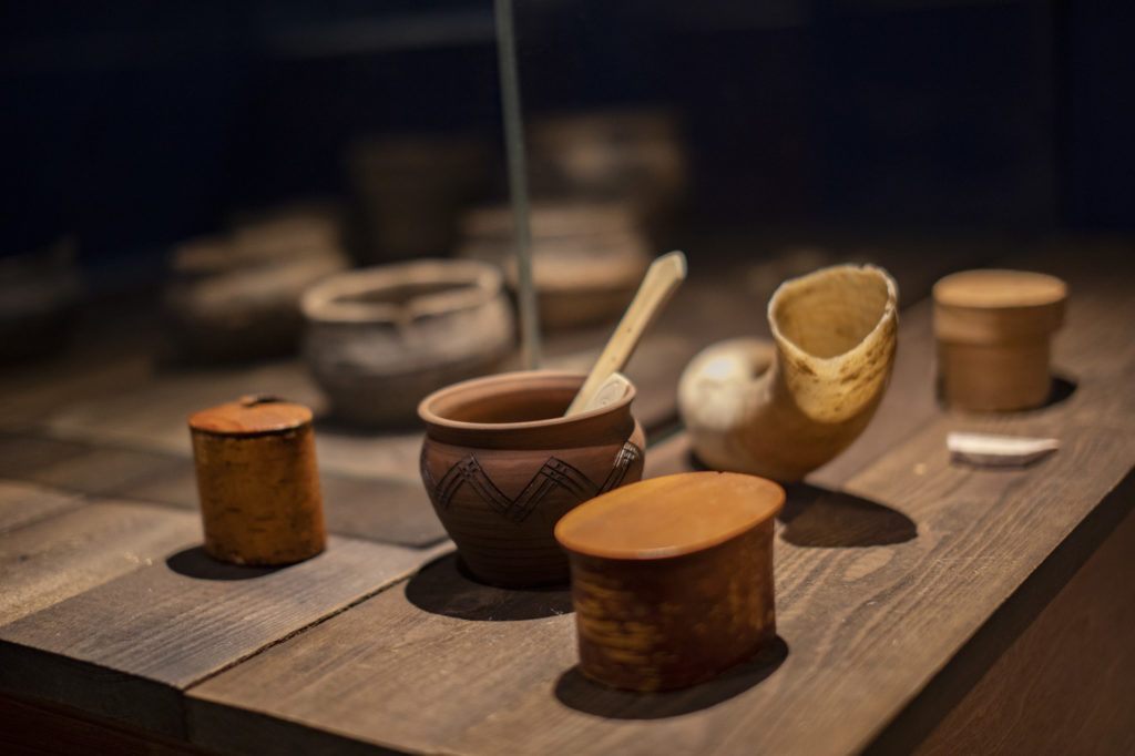 Vanhan mallin mukaan tehtyjä astioita, juomasarvi sekä luusta ja puusta valmistettuja käyttöesineitä. Taustalla vitriinissä aitoja tuhat vuotta vanhoja saviastioita.