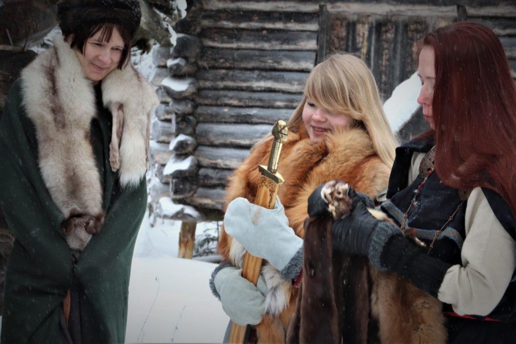 Kolme naista tekevät kauppaa Härkänummen viikinkikylässä talvisessa maisemassa. Takana hirsirakennus.