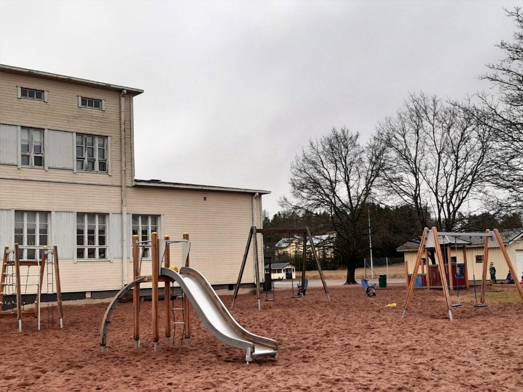 Panelian koulun piha, jossa keinuja, kiipeilytelineitä ja liukumäki