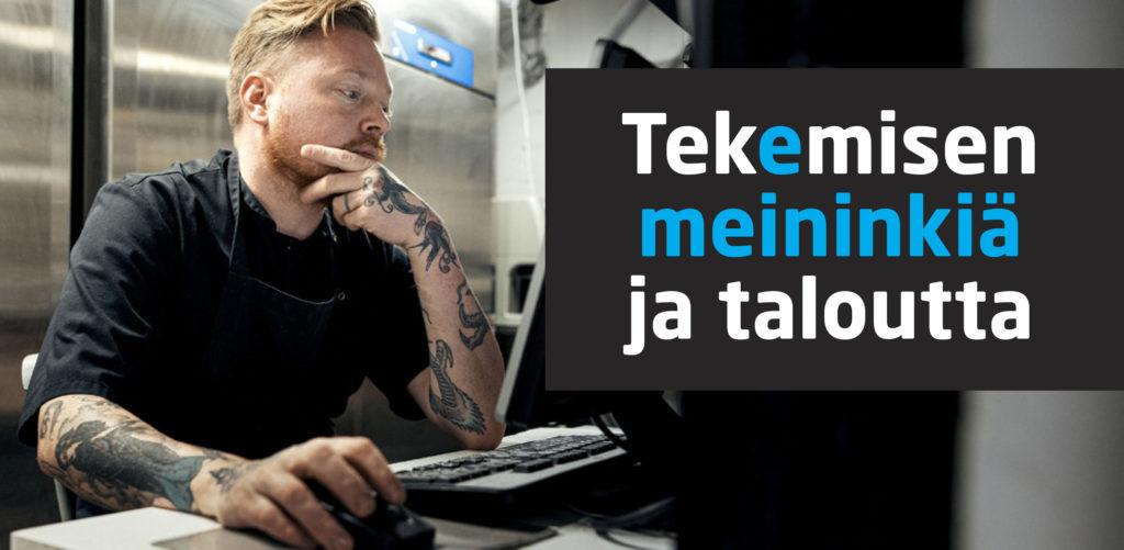 Tatuoitu mies istuu pöydän äärellä tietokoneella