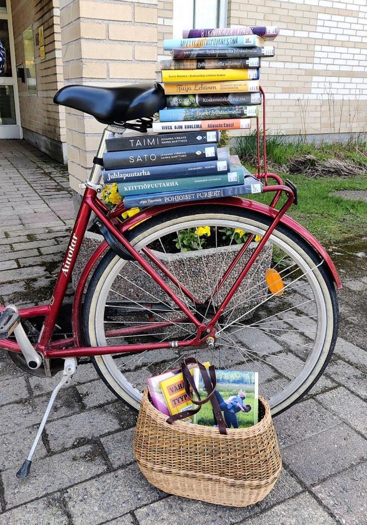 Punaisen polkupyörän tarakalla iso pino kirjoja