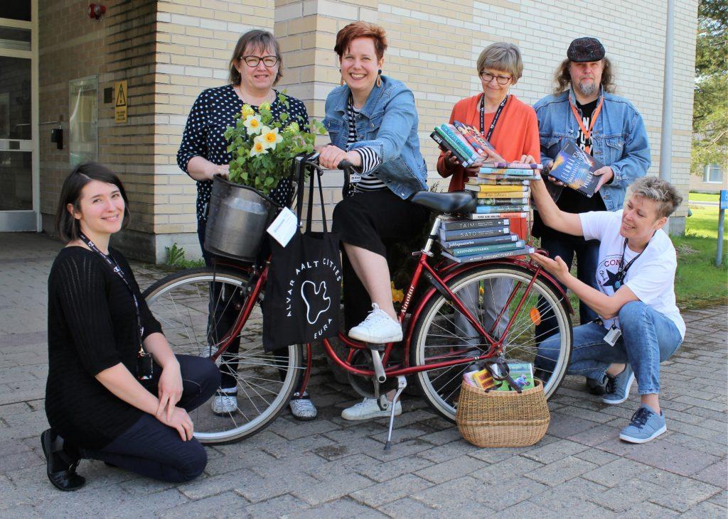 Euran kirjaston henkilökunta pääkirjaston edessä. Kuvassa mukana polkupyörä, jonka tarakalla iso pino kirjoja.
