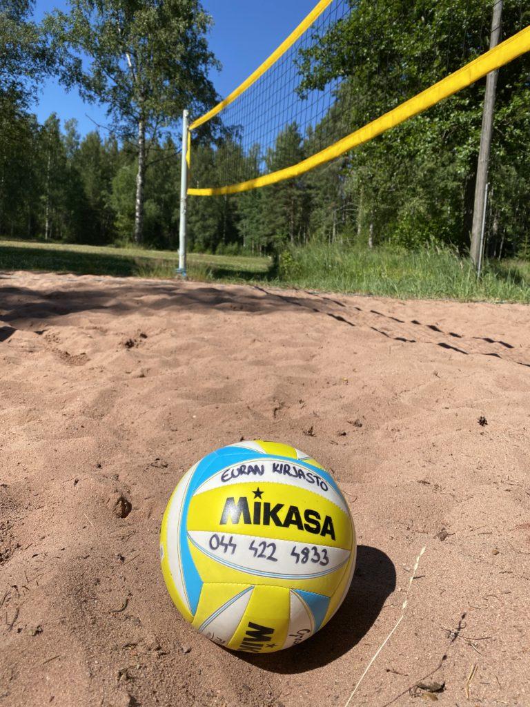 Kuvassa kesäinen rantalentis kenttä, jossa etualalla pallo ja taustalla hiekkakenttä ja verkko