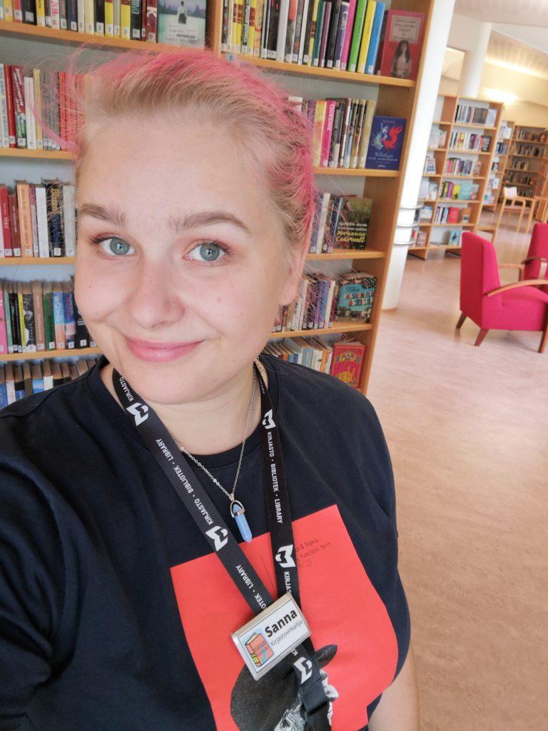 Omakuva kirjaston kesätyöntekijästä, Sannasta, pääkirjaston hyllyjen välissä.